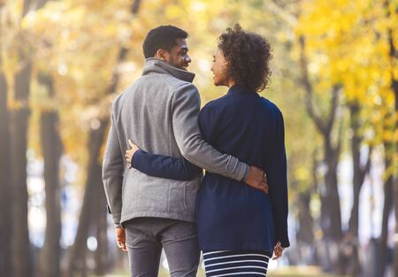 Rear view of young afro guy and girl in love cuddling at autumn forest, walking and talking, copy space