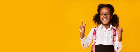 School Win. Excited African American Schoolgirl Gesturing Victory Sign Over Yellow Background In Studio. Panorama With Empty Space