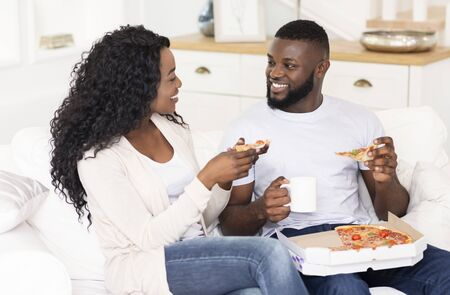 Cheerful african american couple eating pizza and drinking coffee, sitting on couch at home. Stock Photo