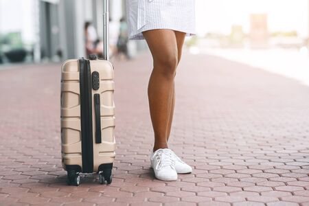 Young black woman with suitcase waiting taxi at airport, free space