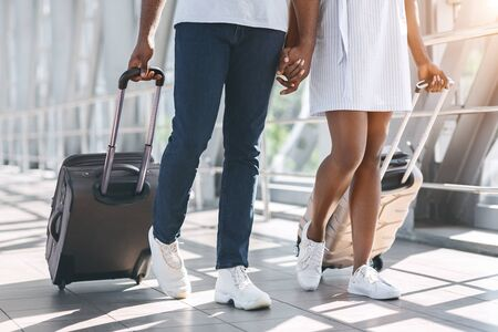 Travel, youth and tourism concept. Black millennial couple walking with luggage at airport building, close up 版權商用圖片