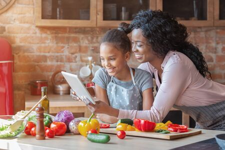 Happy parenthood. Black woman and her cute daughter reading recipe on tablet, cooking at kitchen, copy space