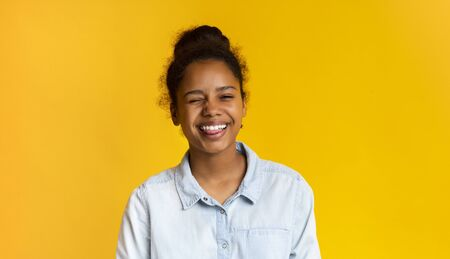 Playful teen girl winking and sticking out tongue on yellow studio background, copy space Banco de Imagens