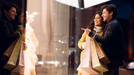 Couple looking at fashion stores window, shopping together and walking near city center