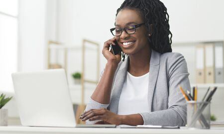 African American Business Woman Having Phone Conversation Working On Laptop In Modern Office. Empty Space Фото со стока
