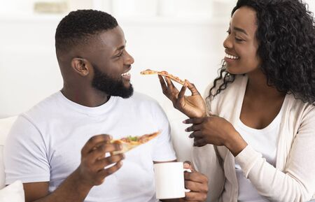 Lovely black millennial couple sharing pizza and drinking coffee on date at home