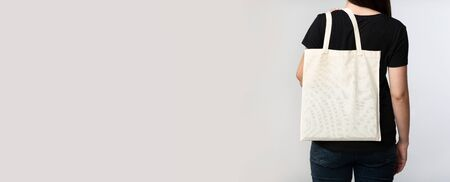Ecology Concept. Unrecognizable Woman Holding Eco Bag Standing With Her Back To Camera On White Background. Panorama, Cropped, Copy Space