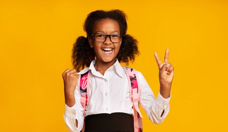 Excited Black Elementary School Girl Gesturing Victory Sign On Yellow Studio Background. Little Winner Concept