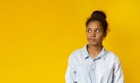 Annoyed african teen looking aside at free space on yellow studio background. Banque d'images