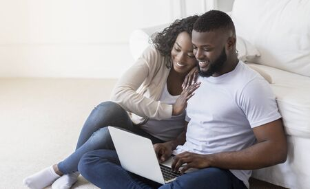 Young african couple web surfing on laptop sitting on floor at home, relaxing, copy space