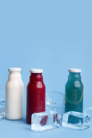 Close up of three different types detox drinks on blue background with ice cubes and copy space