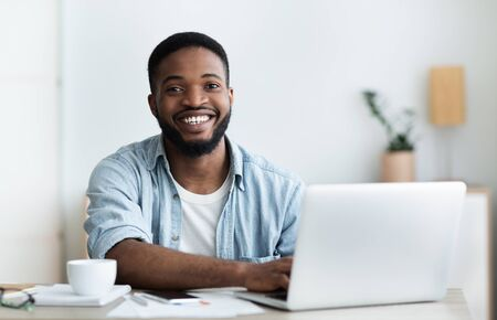 Portrait of handsome african worker using laptop, smiling and drinking coffee at workplace in modern office. Free space