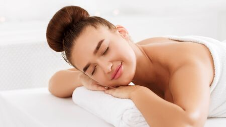 Health spa. Woman lying with closed eyes, relaxing and waiting for masseur