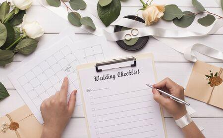 Femme écrivant des articles de mariage dans la liste de contrôle pour le budget de planification, panorama