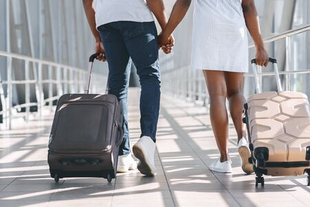 On way to vacation. African couple walking in airport with suitcases, close up 版權商用圖片