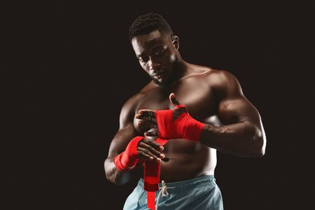 Young african boxer preparing for fight, wrapping hands with red bandage, copy space