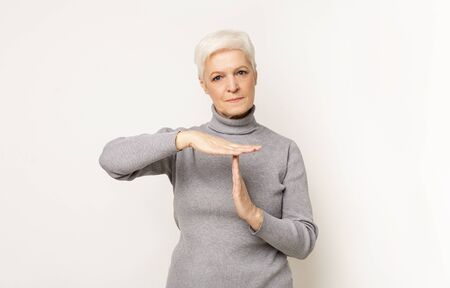 Body language. Impatient senior woman making time out gesture, light studio  with copy space.