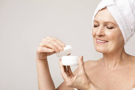 Aged beauty. Smiling aged woman holding open jar of face cream, closeup 스톡 콘텐츠