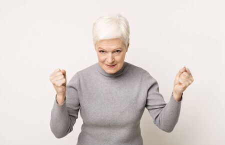 Angry elderly lady threatening someone with raised clenched fists, copy space