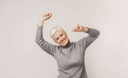 Positive aged lady dancing and smiling over light studio