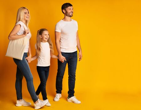Positive Family Of Three Walking Holding Hands Spending Time Together On Yellow  In Studio