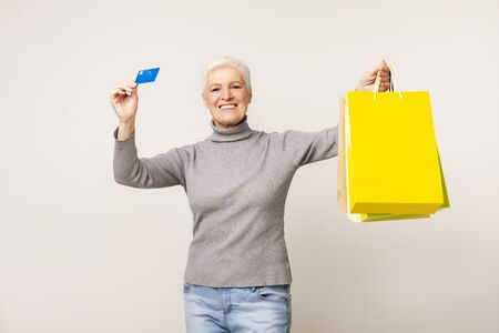 Easy shopping. Joyful elderly woman demonstrating credit card and bright paper bags over light studio