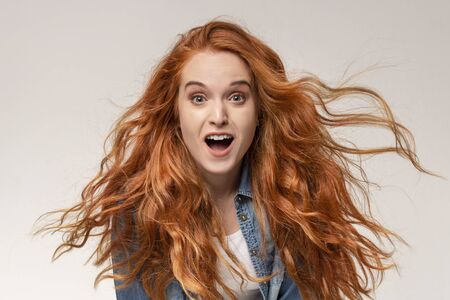 Unbelievable. Shocked millennial redhead girl looking at camera with amazement, light  with copy space