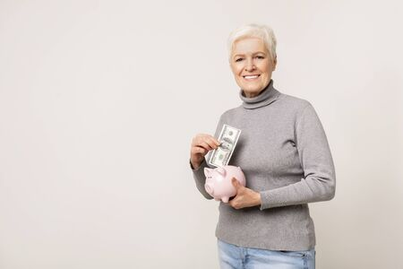 Gain and savings. Smiling senior woman putting money to her piggy bank, light studio  with empty space