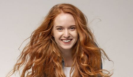 Portrait of cheerful beautiful redhead girl laughing, looking at camera on light Stok Fotoğraf