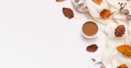Autumn frame with coffee and bright fallen leaves on white
