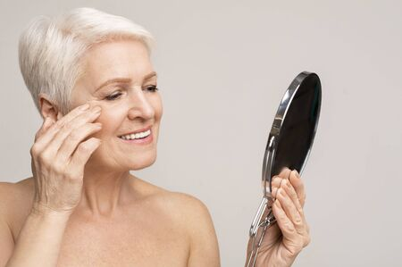Beautiful senior lady looking at mirror and applying anti-aging cream, copy space 스톡 콘텐츠