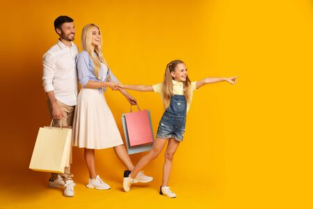 Little Girl Pointing Finger At Copy Space During Family Shopping With Parents Over Yellow