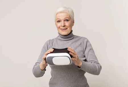 Modern technology and senior age. Elderly woman amazed of experiencing virtual reality after using VR headset