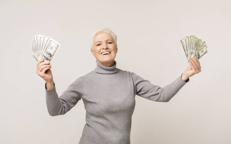 Big Luck. Excited Senior Lady Holding Plenty Of Money In Both Hands On Light