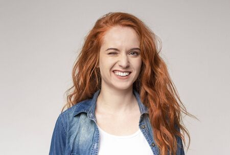 Pretty young redhead girl winking at camera over light studio Stock Photo