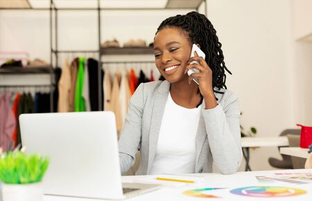 Smiling Clothing Designer Talking On Cellphone With Clients In Showroom. Fashion Business Networking. Stock Photo