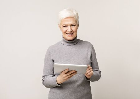Beautiful smiling senior woman holding digital tablet and looking to camera Stock Photo