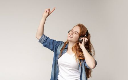 Favorite song. Happy young redhead woman listening music with closed eyes and finger up while standing against light studio