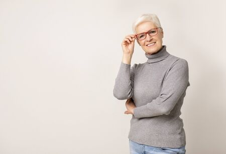 Smiling senior woman wearing glasses and posing to camera, copy space Stock Photo