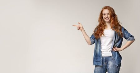 Confident young woman pointing aside at copy space on light