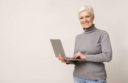 Smiling senior woman using laptop, browsing internet while standing against light studio