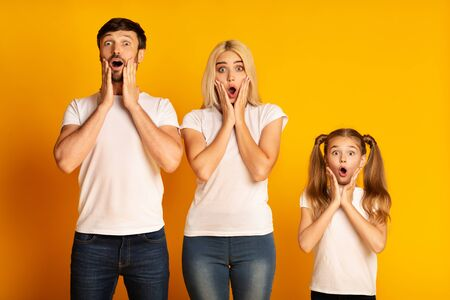 Omg. Shocked Parents And Daughter Looking At Camera With Open Mouth Touching Face Over Yellow