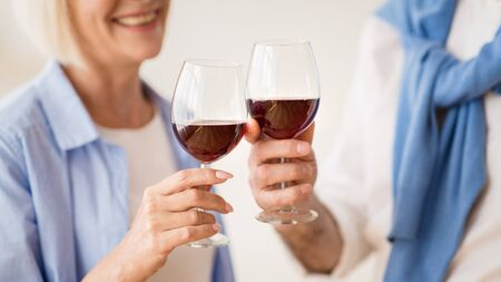 Mature couple clinking glasses of red wine, celebrating anniversary at home 스톡 콘텐츠