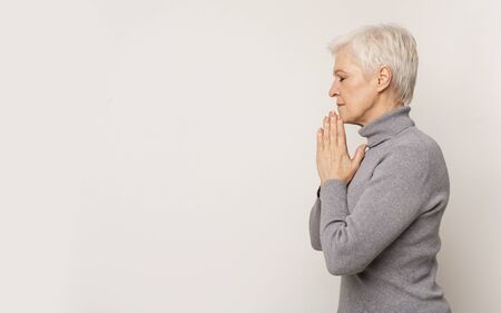 Beautiful mature lady praying with hands clasped near face. 스톡 콘텐츠