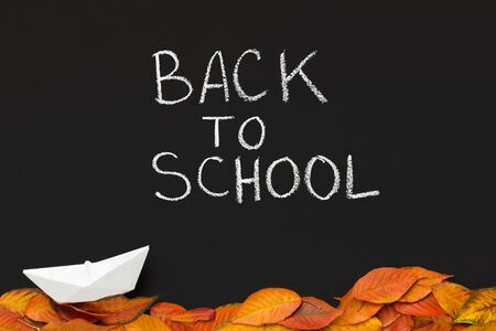 Back to school creative autumn  with paper ship and fallen leaves on chalkboard
