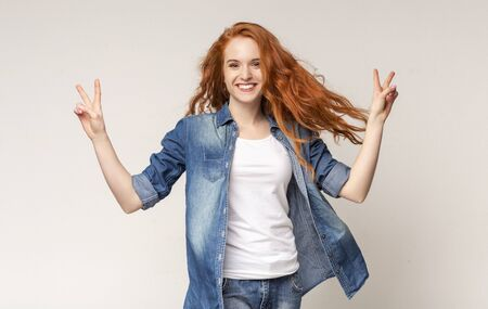 Peace concept. Cheerful teen girl smiling and demonstrating v-sign over light