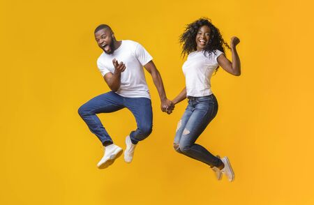 Joyful black couple having fun over yellow background, jumping in the air, guy pointing at camera Фото со стока