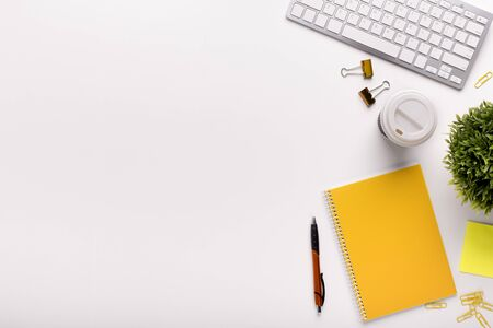 Minimalism on workplace. Office table with yellow notes and white keypad, copy space