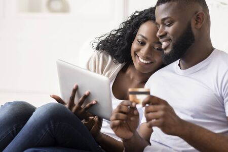 Cheerful Black Spouses Shopping Online Using Digital Tablet At Home, Entering Credit Card Security Code