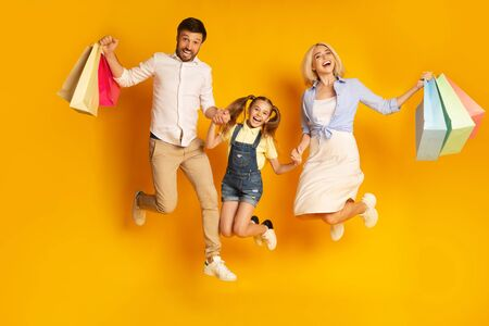 Shopping Together. Happy Family Of Three Jumping Holding Shopper Bags Over Yellow Studio Background.